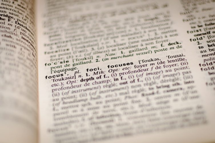 An open dictionary with the word focus in focus