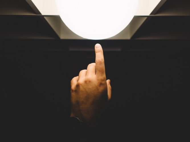 finger touching a lamp in darkness